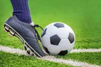 foot kicking soccer ball representing ncaa d1 soccer programs