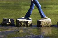 Person crossing stepping stones representing steps to finding merit scholarships