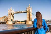 student looking at London bridge representing paying for college in Europe
