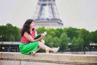 student sitting in front of Eiffel tower rerpresenting requirements for applying to college abroad